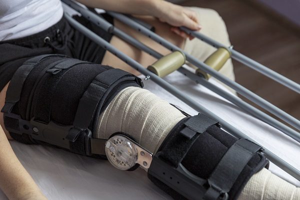 Man in leg brace with crutches - close up of leg