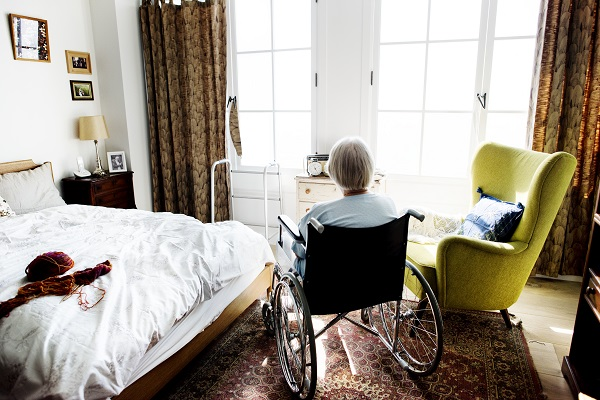 Elderly woman, alone and in a wheelchair, sitting in her room